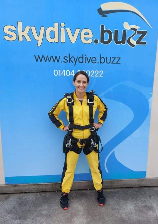 Amy stands in front of the blue Skydive Buzz sign