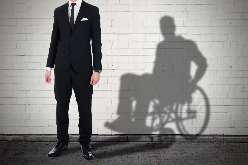Businessman standing against white brick wall with shadow of a person sitting on wheelchair